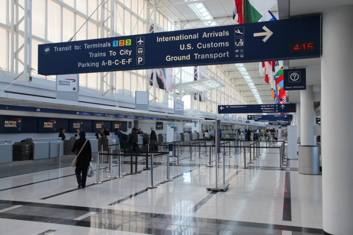 Travelers check in at Chicago O'Hare International Airport while directional signs hang overhead.